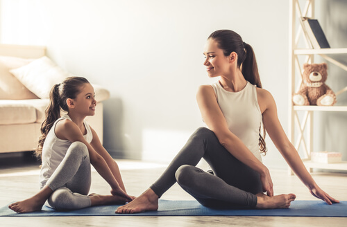 young woman and her charming little daughter are smiling while doing yoga together at home-img-blog