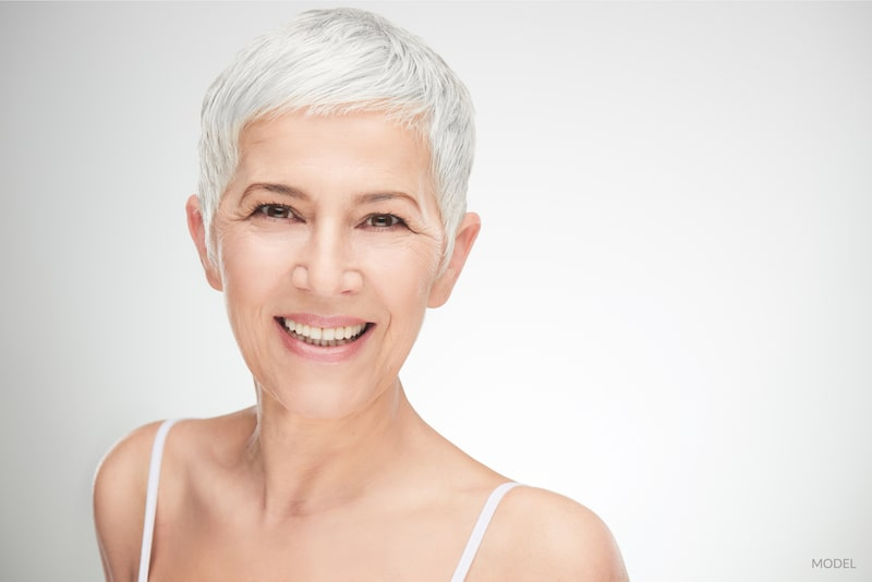 Close-up image of a middle aged women with gray hair. Facial rejuvenation concept.