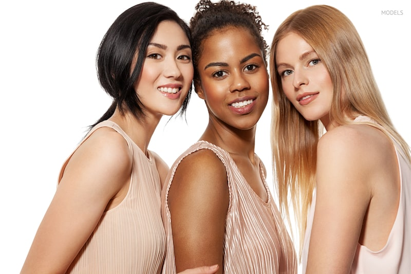 Three young multi-ethnic women huddled together.